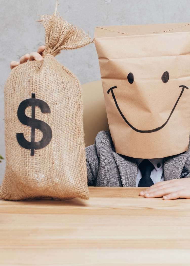 kid with a happy face mask holding a bag with the money sign on it.
