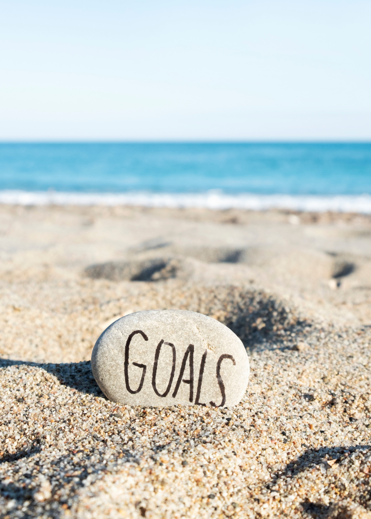 Rock with the word goals on it sitting in the sand at the beach