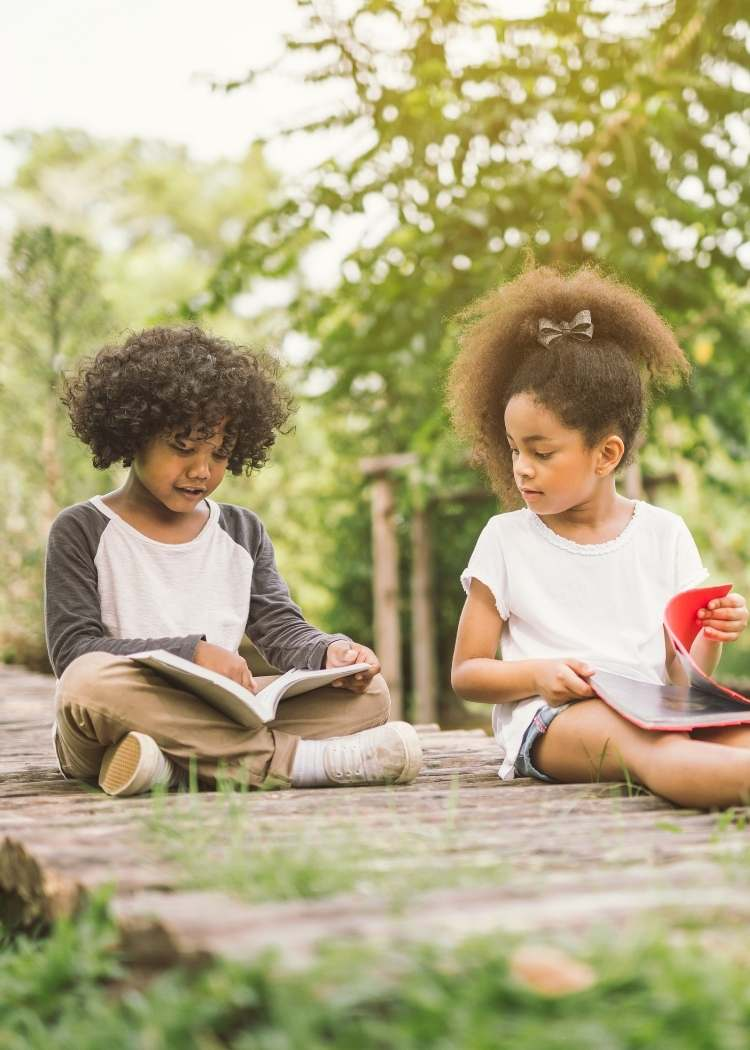Two kids reading outside