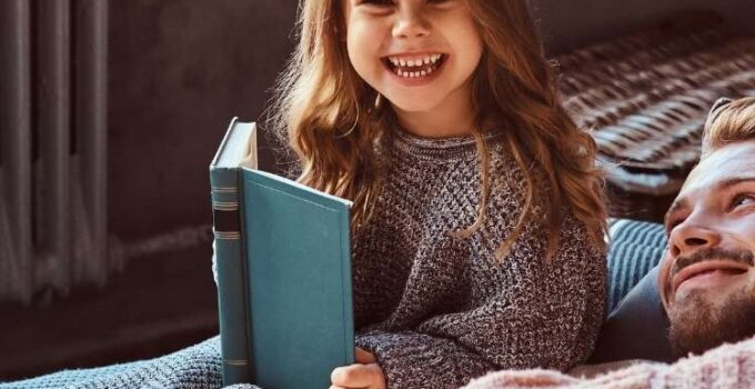 girl holding book smiling next to her dad