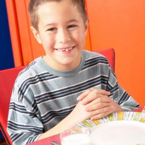 boy sitting at thable with folded hands and a pleasant smile