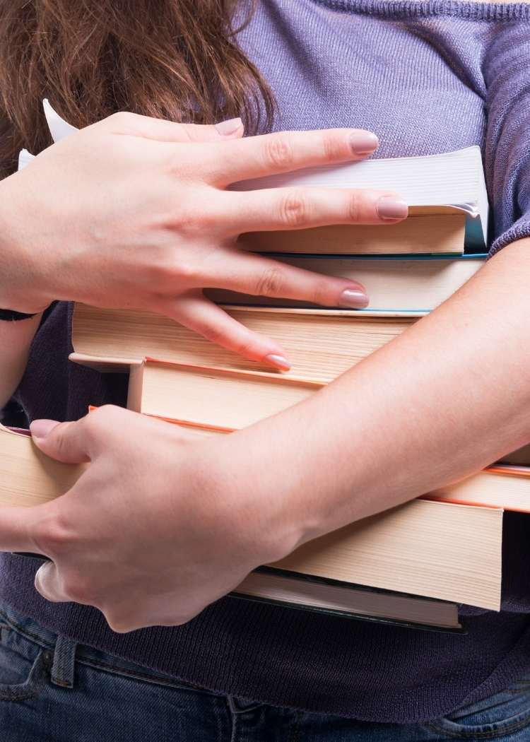 girls hands holding a pile of books