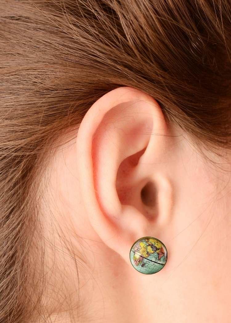Close up of woman's ear wearing globe earrings