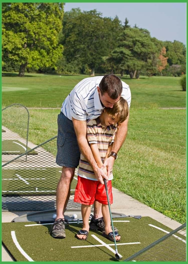 Dad teaching son how to hit a golf ball