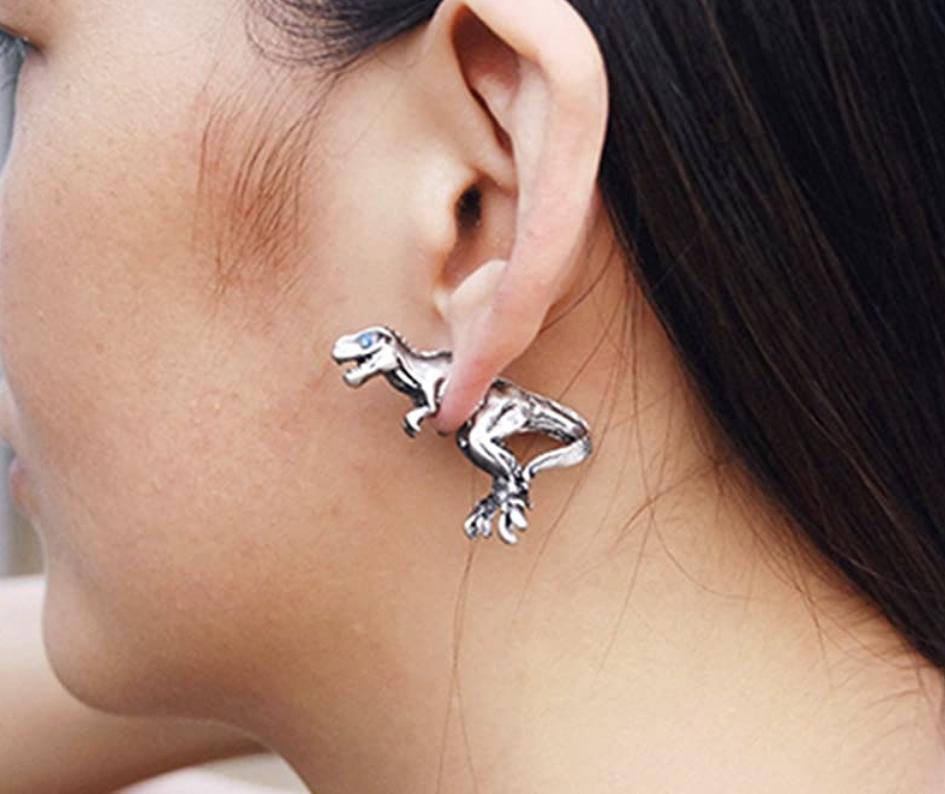 Close up of woman wearing dinosaur earrings
