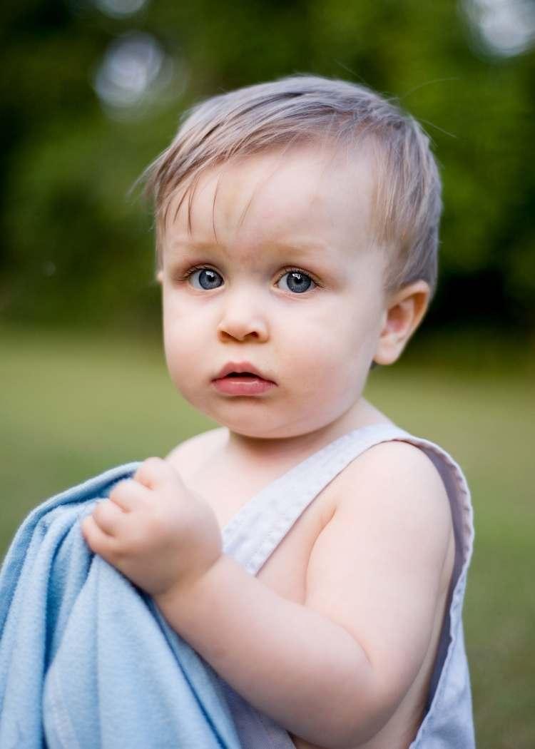 toddler holding blue satin blanket