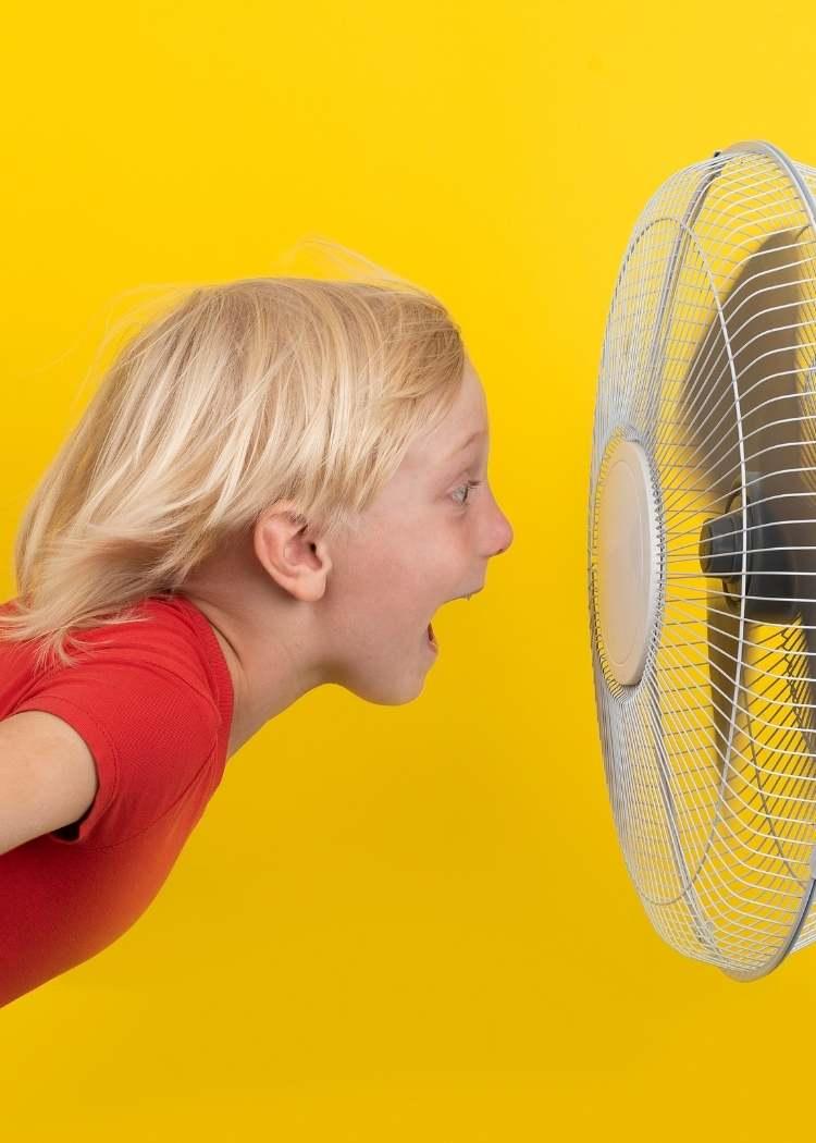 child yelling into fan